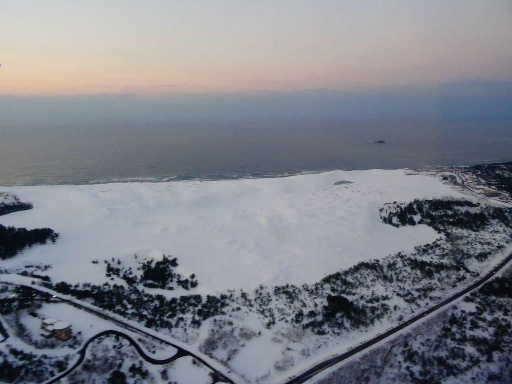 今日も一日お疲れ様! 飛行機から見える雪の砂丘。一面真っ白な大雪原。 日本海に落ちる夕陽と相俟った素…