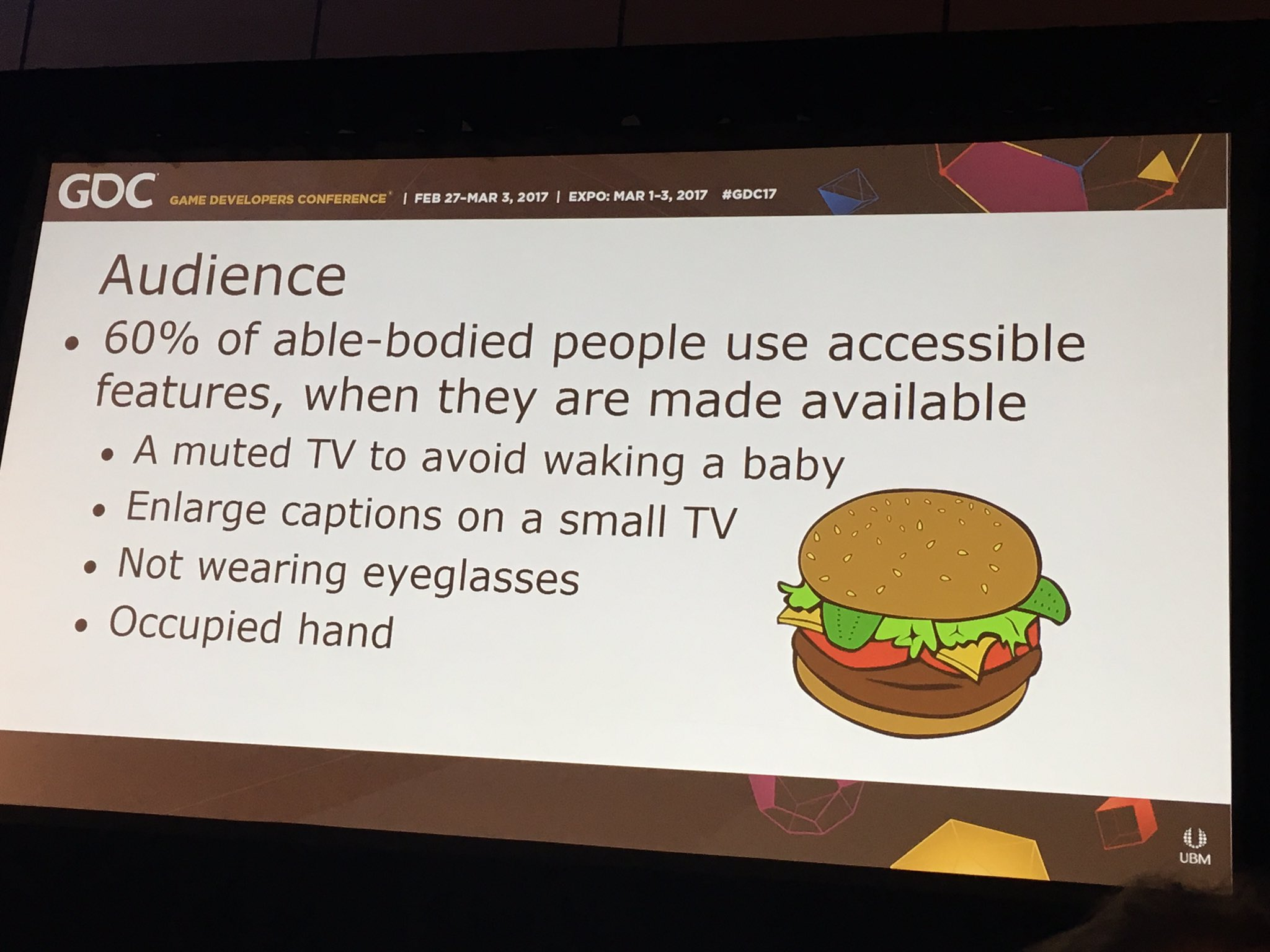 GDC slide that reads Audience: 60% of able-bodied people use accessibility features, when they are made available. A muted TV to avoid waking a baby. Enlarge captions on a small TV. Not wearing glasses. Occupied hand.