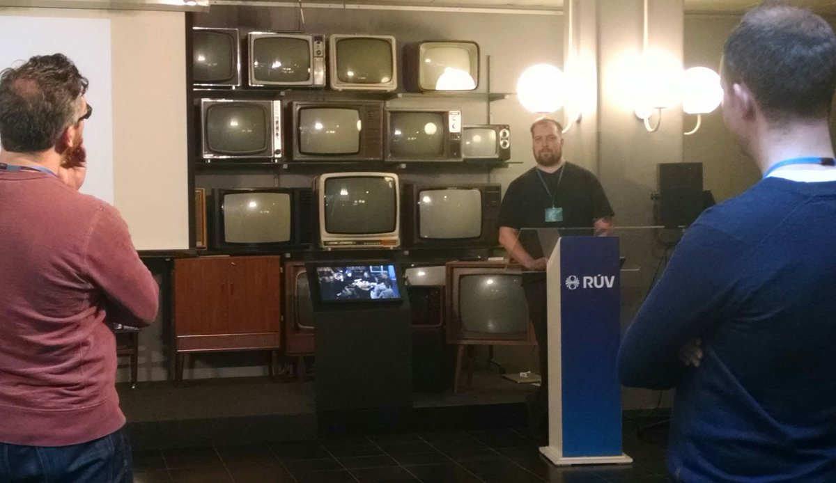 A man giving a talk in front of old televisions