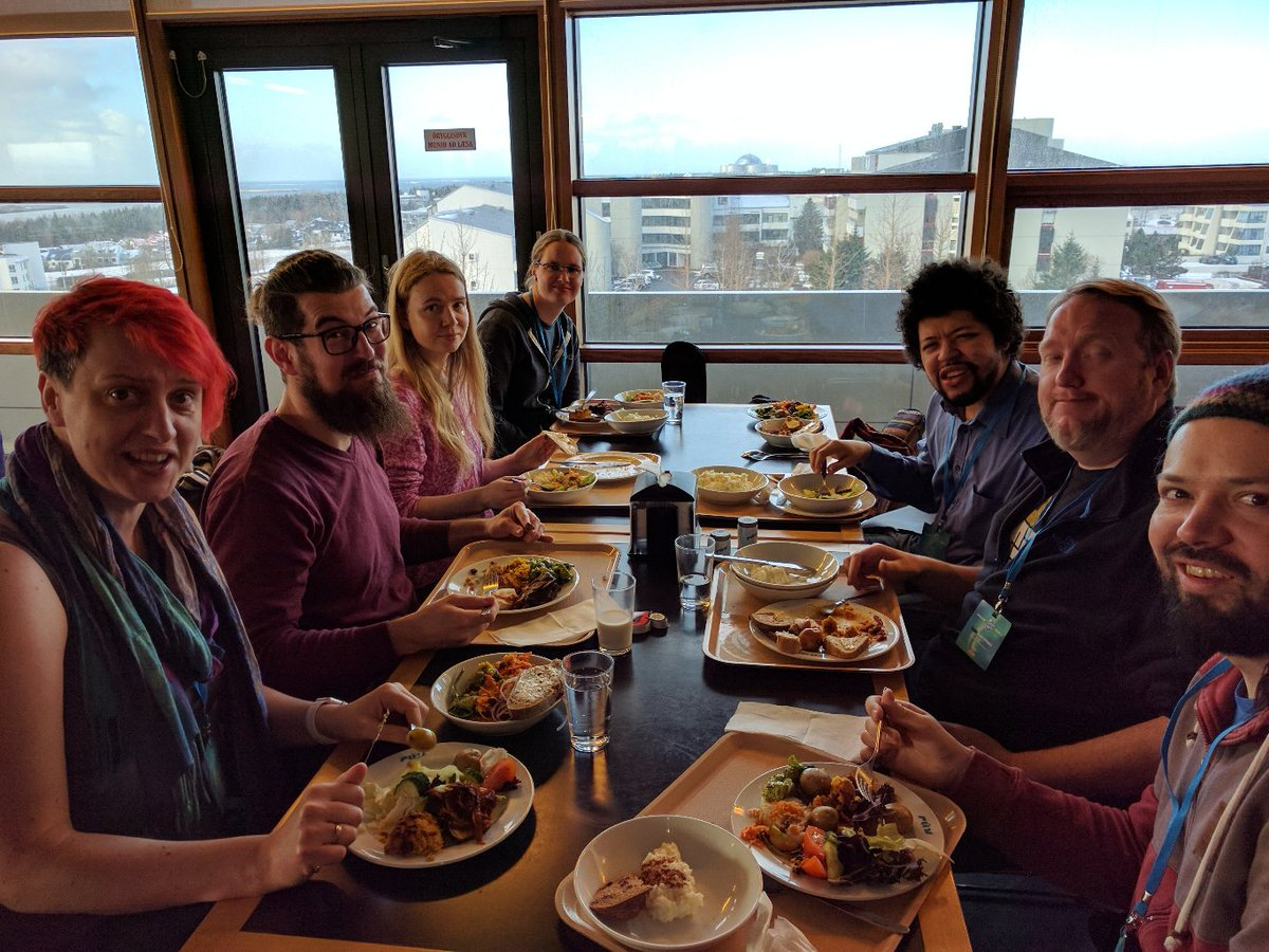 7 people around a table with trays of food, iceland skyline in background