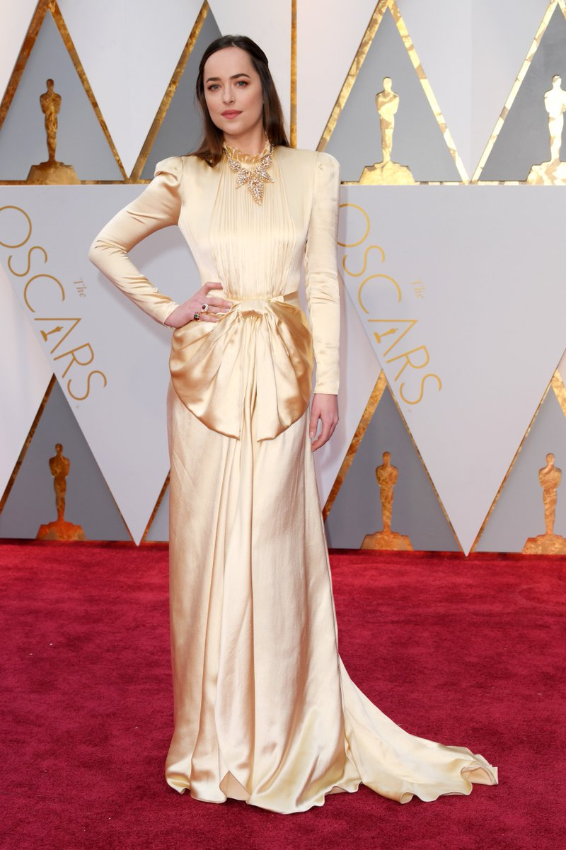 Dakota Johnson is wearing a shade of ivory on the #Oscars red carpet h...