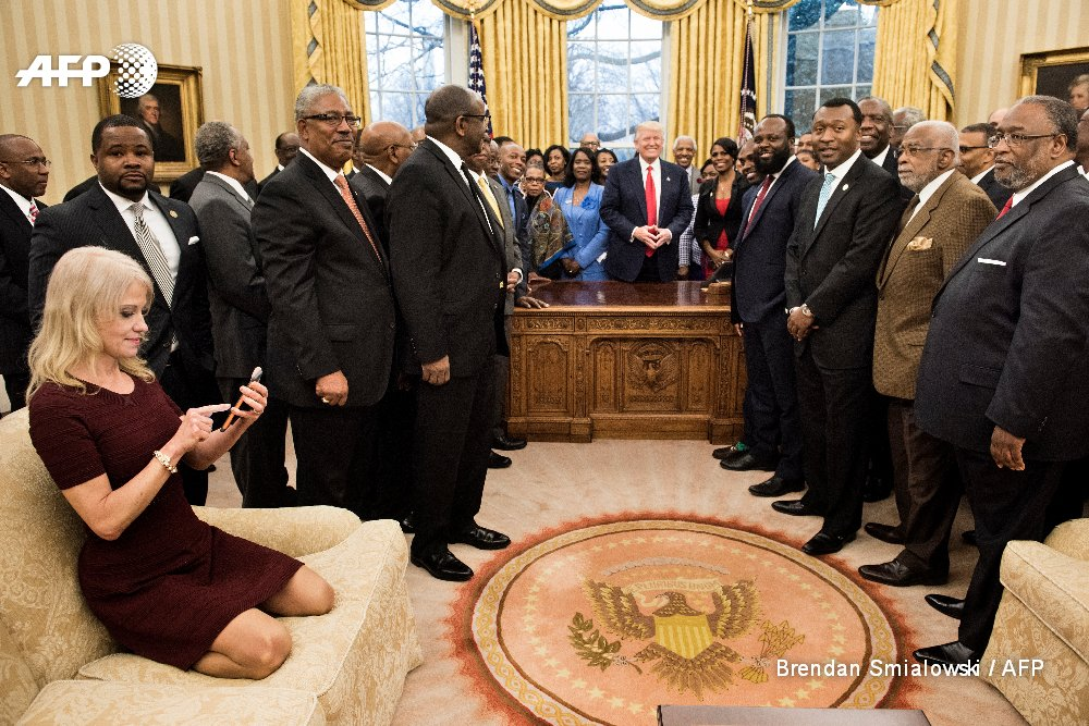 Kellyanne Conway checks her phone after taking a photo of President Donald Trump and leaders of black universities, colleges in Oval Office