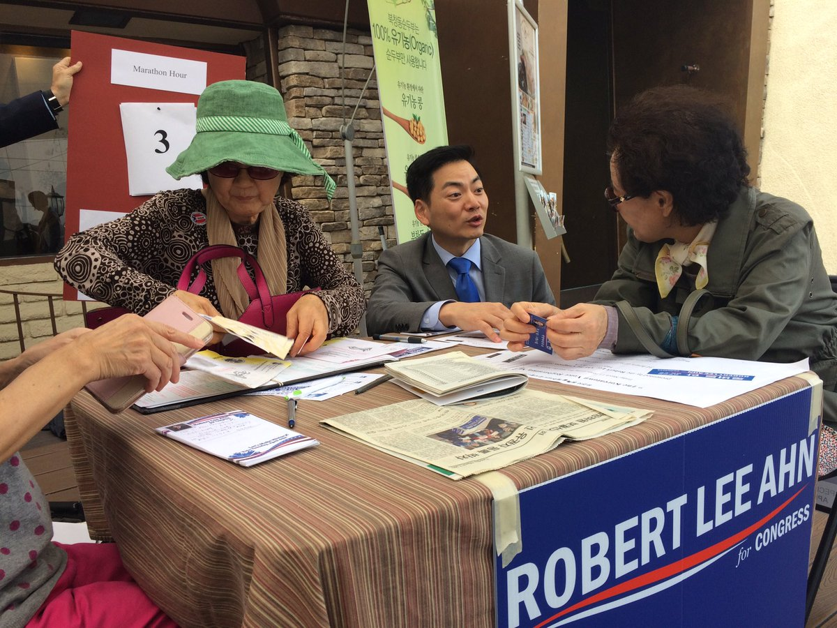 Congressional candidate Robert Ahn, center, speaks to voters at a voter registration drive headed by his campaign. (Christine Mai-Duc / Los Angeles Times)