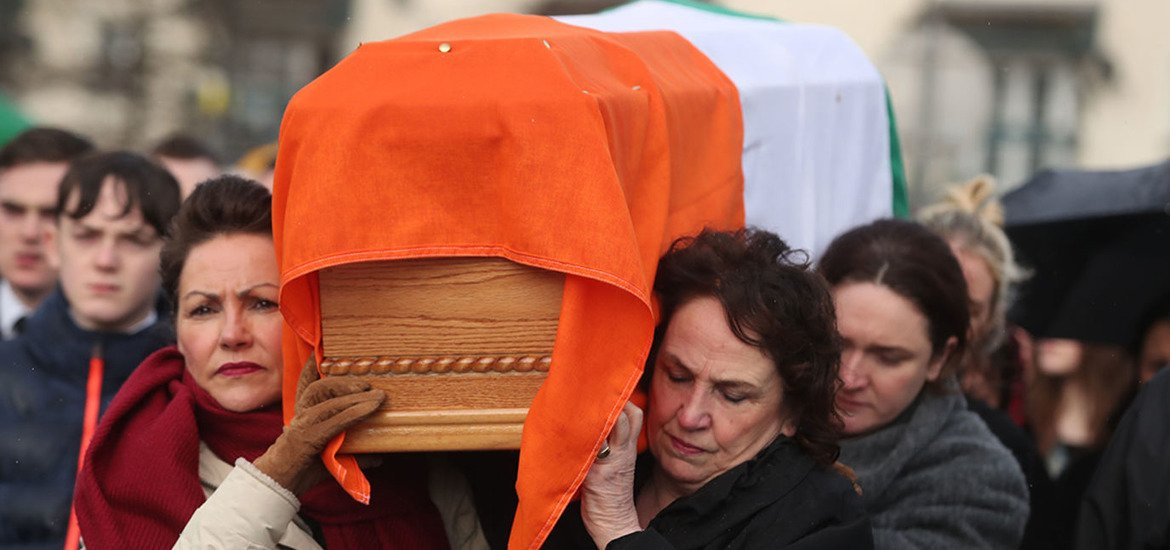 Martin McGuinness's wife carries his coffin as his remains return home...