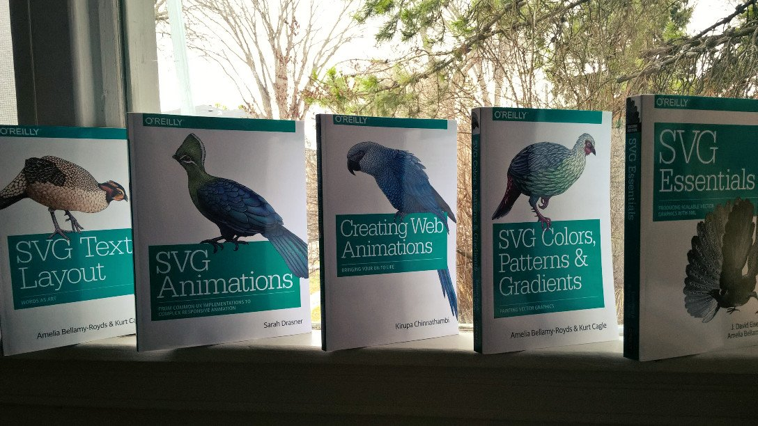 Five O'Reilly books lined up on a windowsill: SVG Text layout, SVG Animations, Creating Web Animations, SVG Colors, Patterns & Gradients, and SVG Essentials.  Each has a different exotic bird on the cover. The last bird-book is the oldest, and shows it by only being in black & white. The colourful animals on the other books reflect full-colour figures inside.