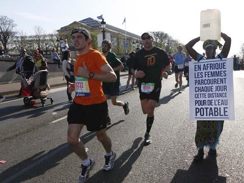 Une Gambienne prend le départ du marathon de Paris en marchant, un bidon d'eau sur la tête http://t.co/J5KTCBVZu6