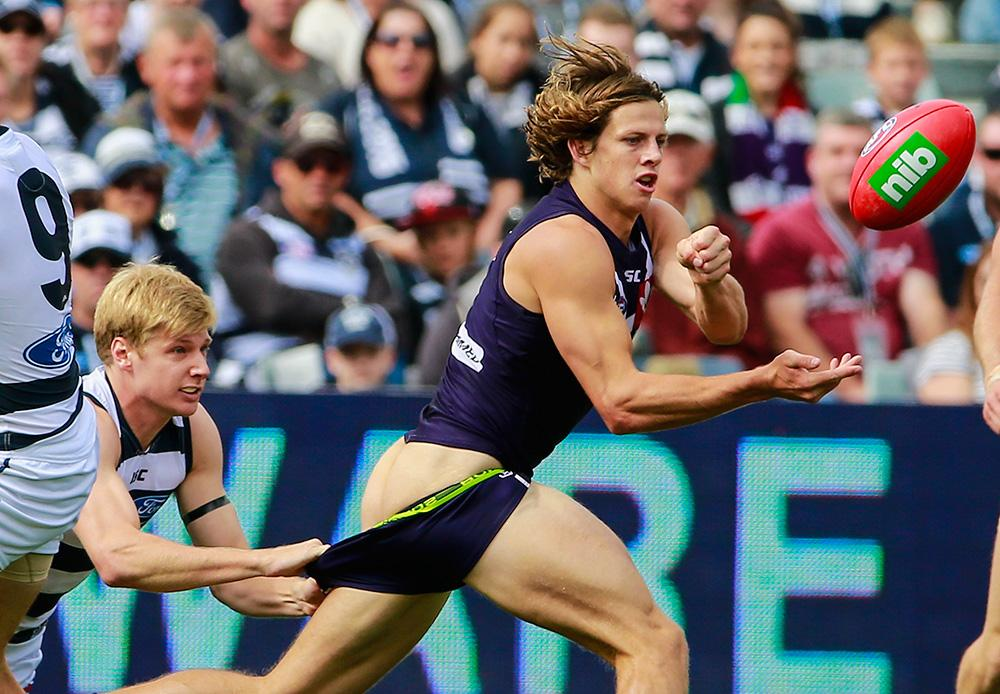 Lachie Neale of the Dockers kicks the ball as Nathan Fyfe