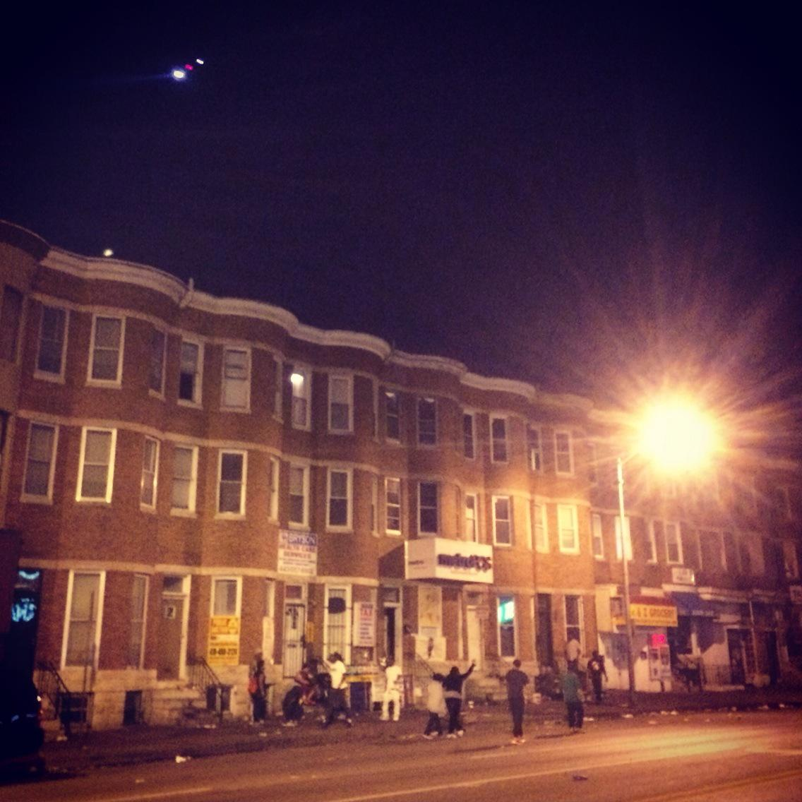 "10PM, #Baltimore curfew in effect, police helicopter circling, saying ppl will be arrested. Ppl below yell ""f*** u"" http://t.co/ntY9krptOY"