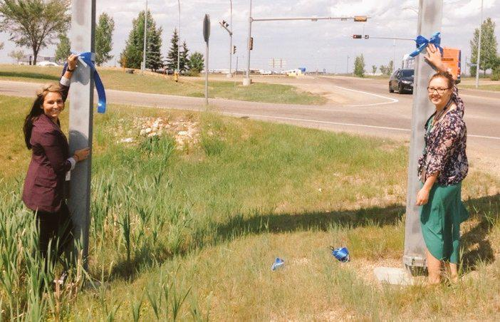 EIA staff members hang blue ribbons along the highway in support of #EPSstrong #yeg @edmontonpolice http://t.co/0crqiIXGkV