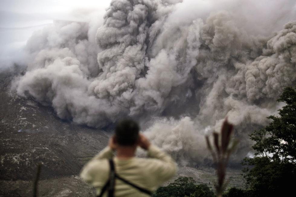 FOTO Un uomo osserva il fumo fuoriuscire dal vulcano Sinabung da Tiga Serangkai, in Indonesia