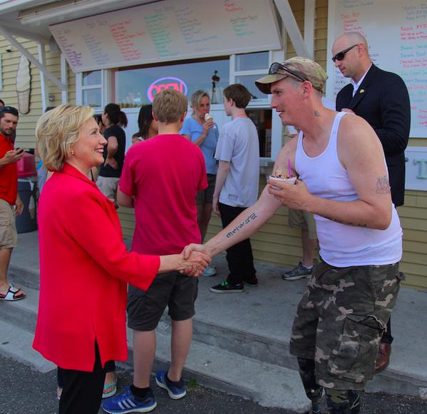 Hillary Clinton shakes hands with man white tattoo