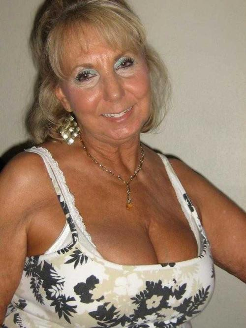 image Grandmother with large breasts pushes huge dildo inside
