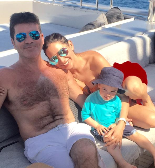 Simon Cowell sitting on a couch with his girlfriend, Lauren Silverman and son Eric