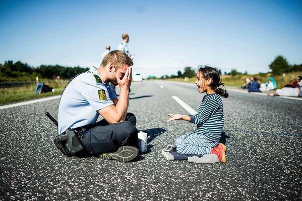 "A Danish police officer plays ""peek a boo"" with a young refugee girl http://t.co/ZLPg9dkoUB"