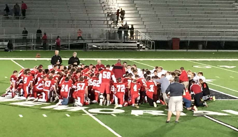 Wahoo Neumann and @NorfolkCatholic players pray with Fr. Dan Andrews after last night's game. #CatholicEdChat http://t.co/fmkzOupd3a