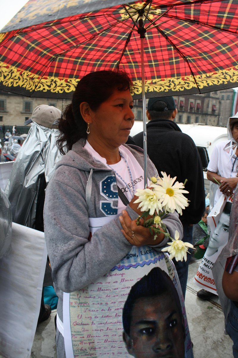A mother of a missing #Ayotzinapa student holds flowers as it rains. It also rained 9/26/14 when they disappeared. http://t.co/EdRPKj4Rpo