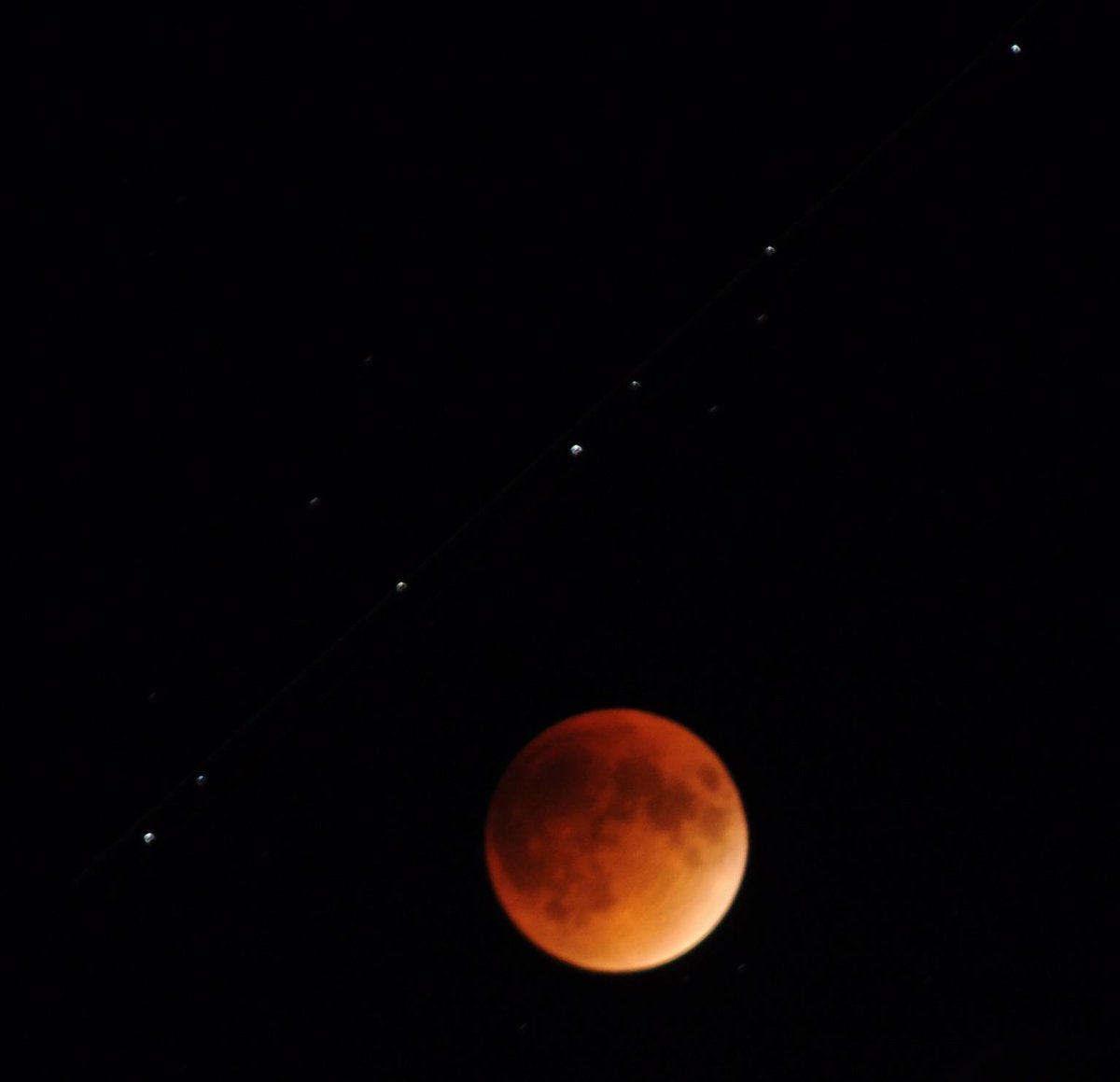 Full #SuperBloodMoon eclipse. F/5.6 4 second exposure, ISO 800. Caught a plane flying by. http://t.co/qwSNV5GfXS