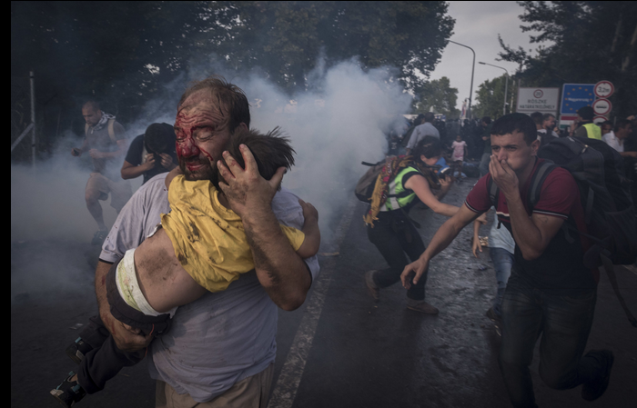 A man tries to save his child as Hungarian police fire tear gas. Photo by Sergey Ponomarev http://t.co/JzkDyknESS http://t.co/vmsHchWIzd