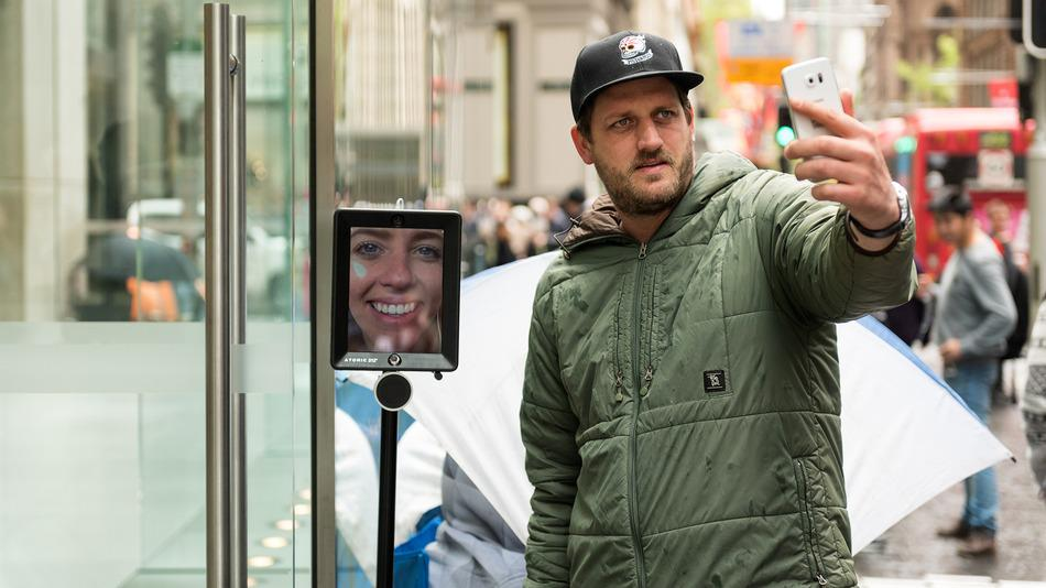 There is a robot waiting in line to get an iPhone 6S outside an Apple Store in Australia