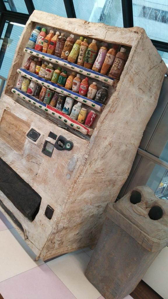 渡り廊下の途中にあった自販機に違和感を持ち、近寄ったら木彫りだった。ゴミ箱も木彫りだった。取り出し口に何かあるのではないかと覗きこみたくなる絶妙なスイング具合。 pic.twitter.com/mX0rKYx8fU