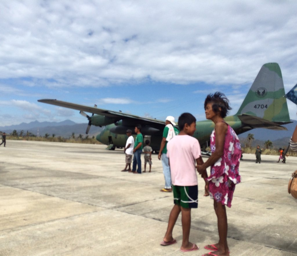 GROUND ZERO. Local residents watch as boxes of relief goods are downloaded from the first C-130 that landed in Casiguran, Aurora, following the landfall on October 18 of severe Typhoon Lando. Photo by Voltaire Tupaz/Rappler.com