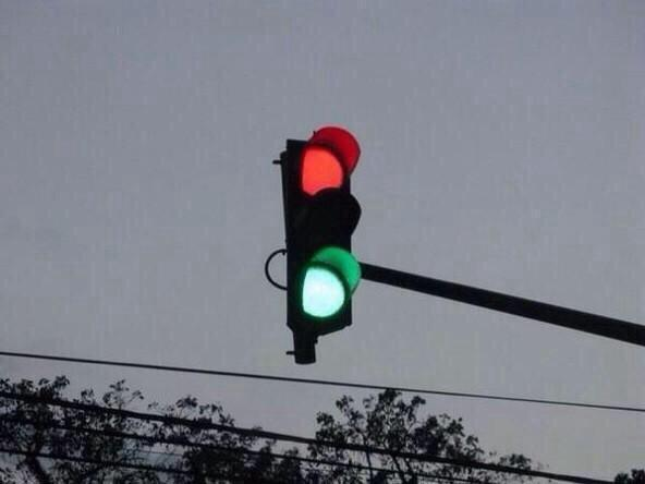 A traffic stoplight with green and red both lit up