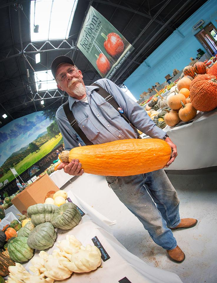 Farmer holding a giant orange squash