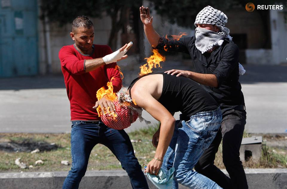 This Is a Photo of a Palestinian Who Lit Himself on Fire With a Molotov Cocktail Intended for Israeli Soldiers. Here's How Reuters Captioned the Moment.