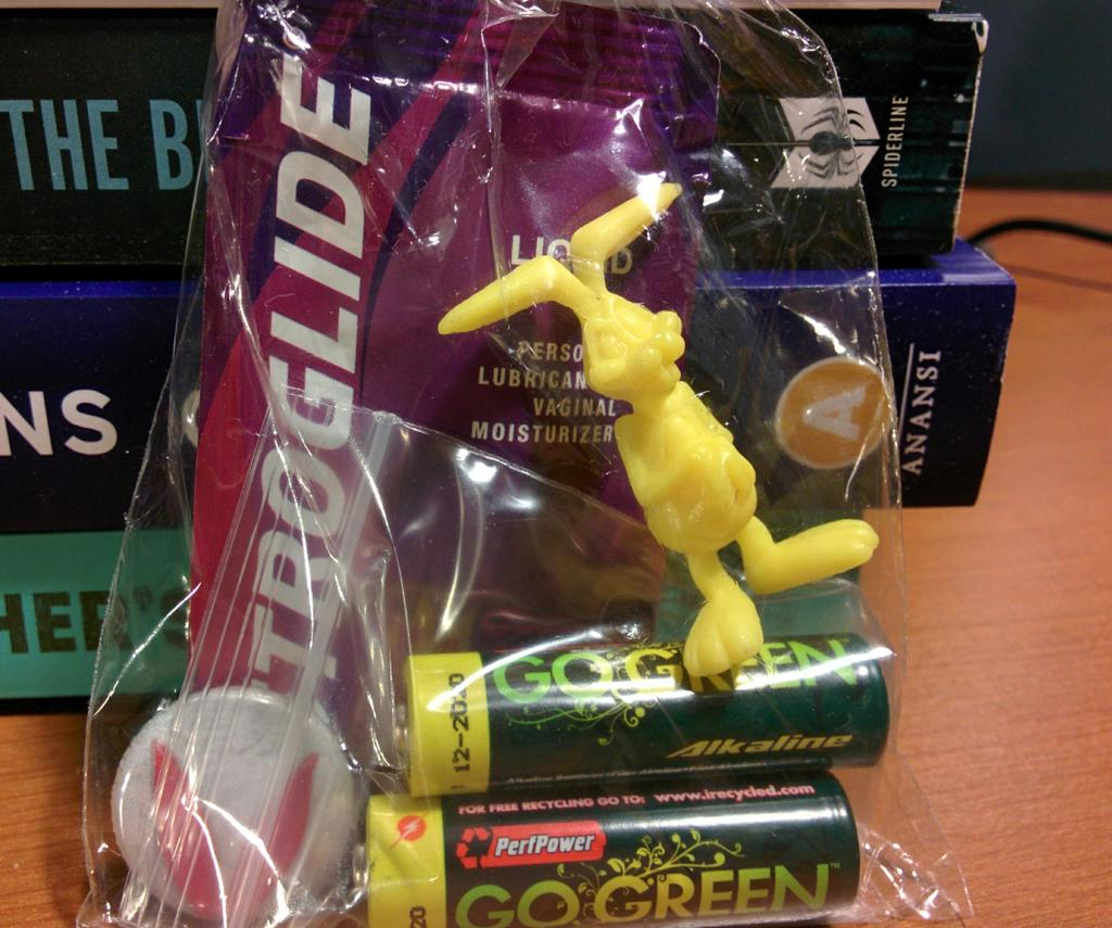 Cellophane bag containing vaginal lubricant, a yellow plastic rabbit, two AA batteries, and a pin