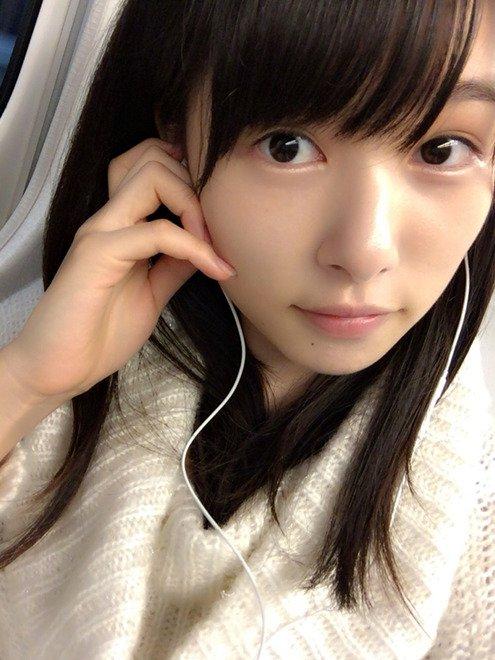 イヤホンで音楽を聴きながらじっと見つめる肌の綺麗な桜井日奈子