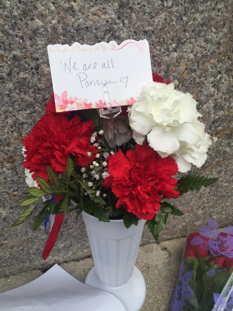 Flowers with tag, 'We are all Parisian'