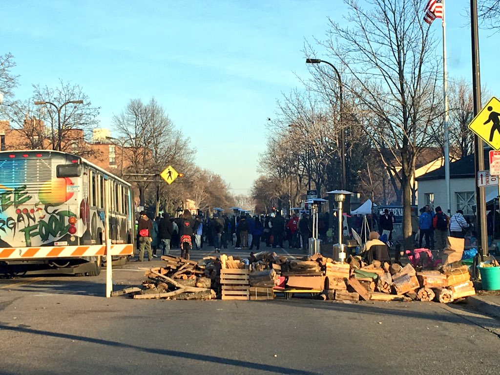Piles of firewood block both ends of the street in front of the 4th District Police Station in Minneapolis