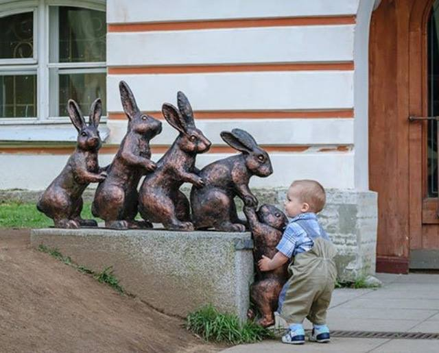 A little boy tries to help the last rabbit up on the ledge. I love this image ridiculously :) https://t.co/fZTk8mYurg