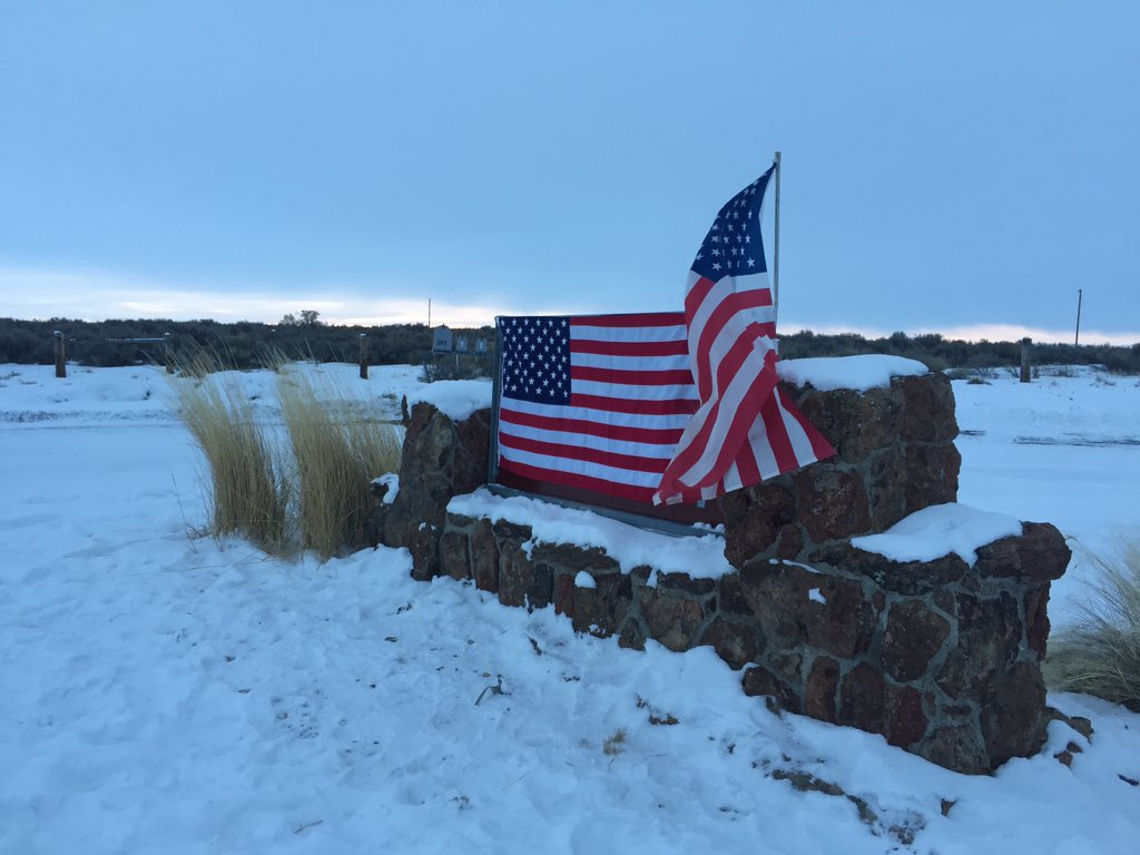 Sign to the Malheur refuge covered with American flags. #BundyMilitia https://t.co/MLT8jsHXmK