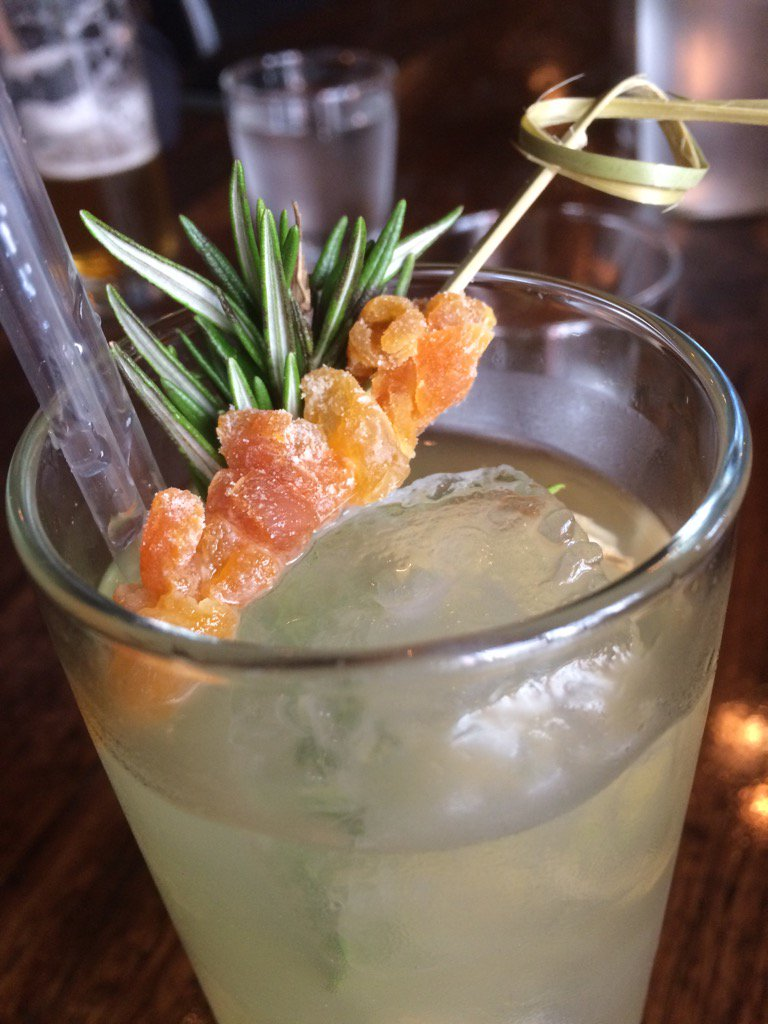 A cocktail with sprigs of rosemary and clumps of skewered ginger