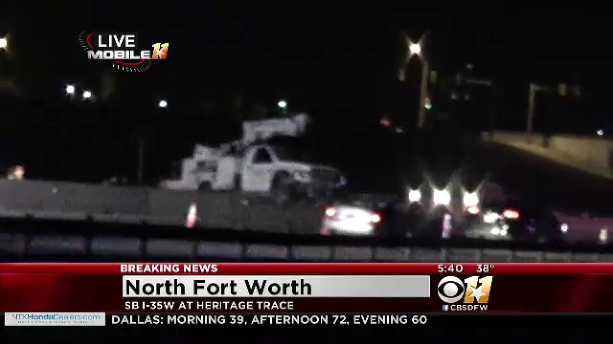 Work truck straddles the barrier wall at I-35W and Heritage Trace. Drivers zig-zagging between two crashes.