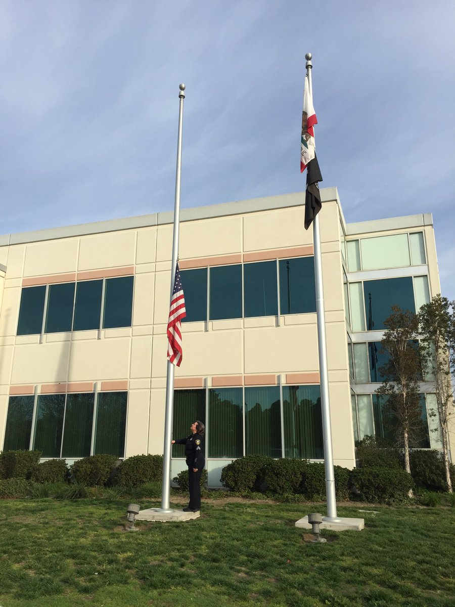 Officer at Richmond PD lowers flag outside station to half-staff. Veteran officer shot & killed. abc7now