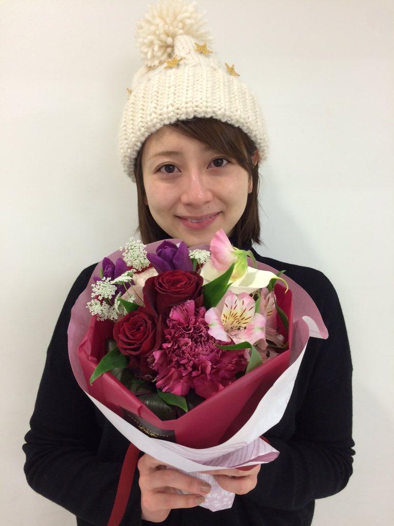 白いニット帽をかぶって大きな花束を持つ大塚千弘