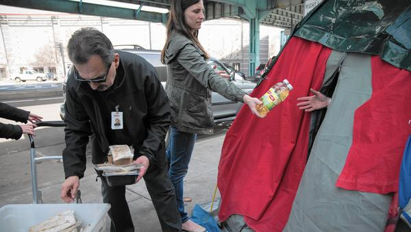 Volunteers are feeding the homeless with the leftovers from catered Super Bowl parties