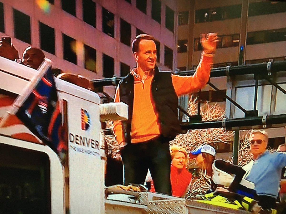 The Sheriff waves to the people of his city as Elway looks on BroncosParade