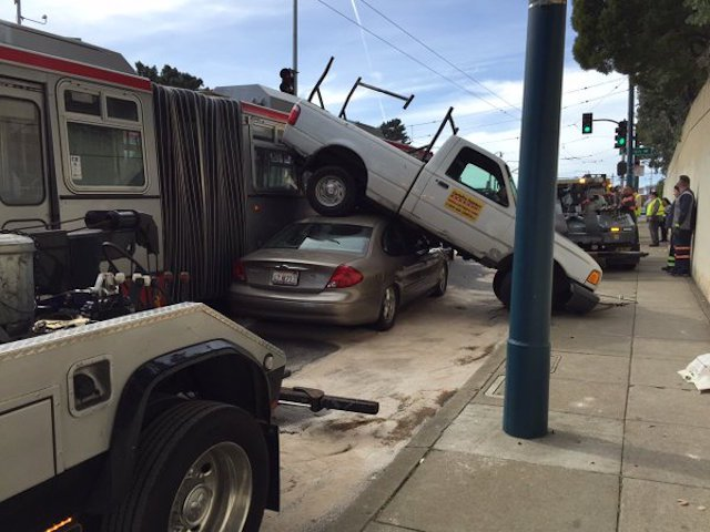 Muni forced to reroute after crash lands truck on top of another car.