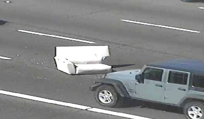 Westbound US 60 near Mesa Drive, there is half a couch sitting between the left and left-center lanes.