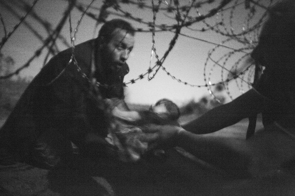 今日発表になった「世界報道写真」の大賞作品。セルビアとハンガリーの国境、赤ちゃんを鉄条網越しに手渡す難民。午前3時。フラッシュを使用できなかったため(警察に見つかる)、月光を使用。 https://t.co/8lZ43MYzw4 https://t.co/Nod51l6q3y