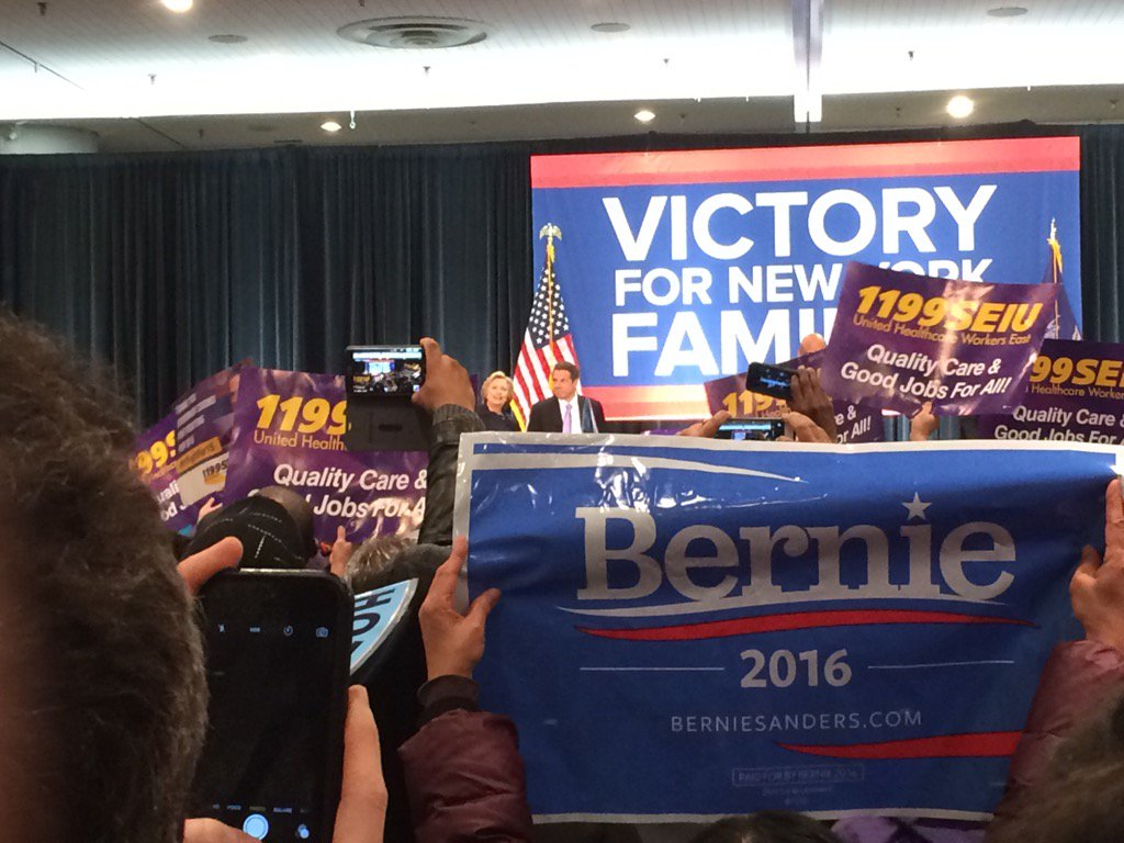 Oopsy. Cuomo event for @HillaryClinton brings out a @BernieSanders sign. https://t.co/PLZirqT2lp