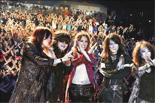 ステージで観客と一緒にXポーズをしているX JAPANの画像