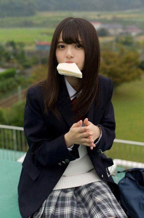 屋上の上でサンドイッチを口にくわえる齋藤飛鳥