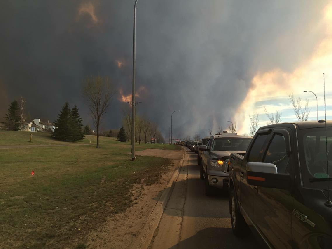 Flames are getting closer but traffic still isn't moving out of #FortMcMurray.Cars are going off road now. #ymmfire https://t.co/f5OxRc7Qui