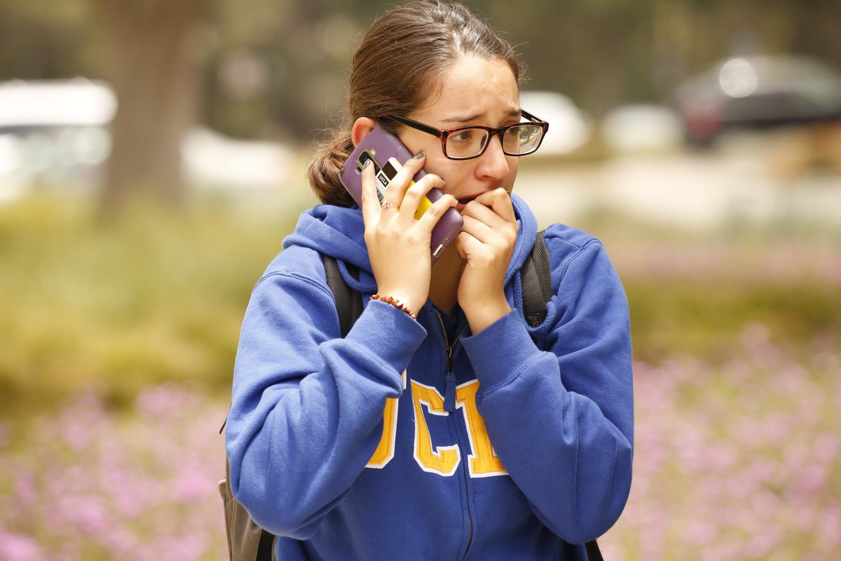 Gabriela Romero calls her mom as students are released on UCLA campus after two people were shot and killed Wednesday. (Al Seib / Los Angeles Times)