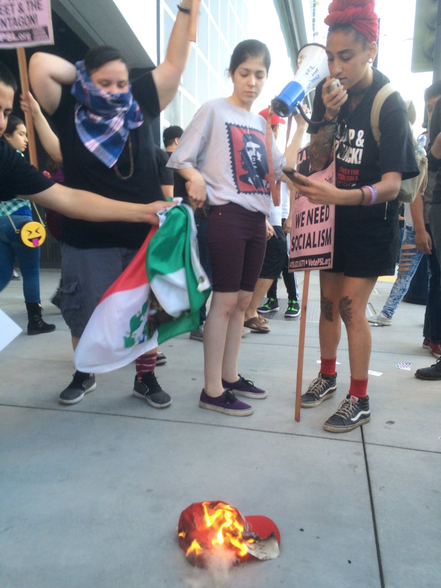Protesters burn a #Trump2016 Make America Great Again hat after rally