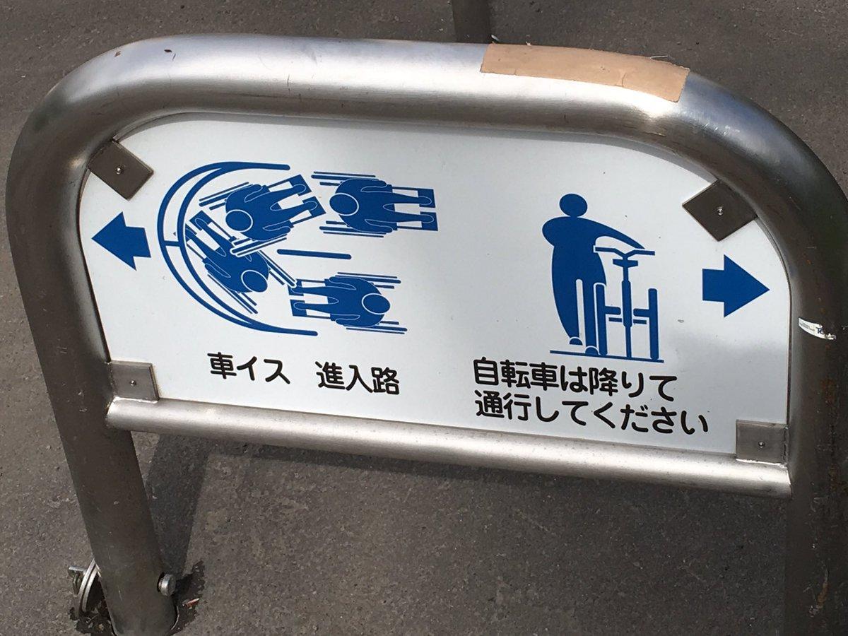 大学の門にある看板、何度見ても車椅子でコーナー攻めてるようにしか見えない。